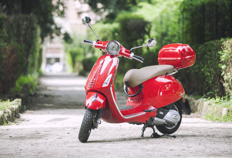 A Red Vespa Primavera 125 for Rent in Rome with a Trail in a Park of Rome in the background.